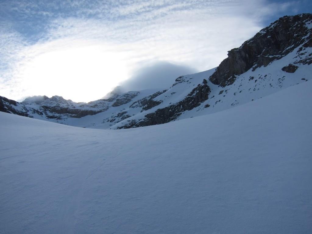 ~ 2850m. a távoli sziklafal alatt kell felmeni jobbra. Kemény a hó. A csúcsot a felhó takarja.